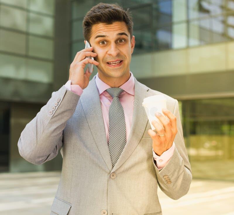 Überraschter Geschäftsmann, der am Telefon spricht lizenzfreie stockfotografie