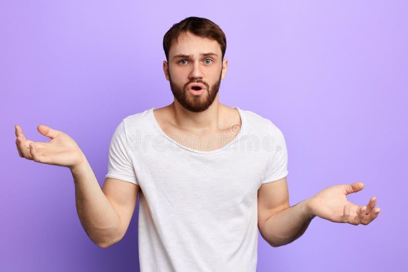Überraschter gut aussehender Mann, der seine Schulter bei der Aufstellung zur Kamera zuckt lizenzfreies stockbild