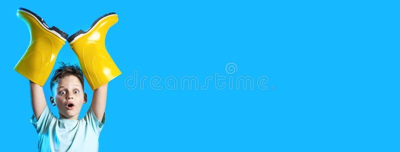 Überraschter Junge in einem hellen T-Shirt haftete seine Hände in den Gummistiefeln auf blauem Hintergrund lizenzfreies stockbild