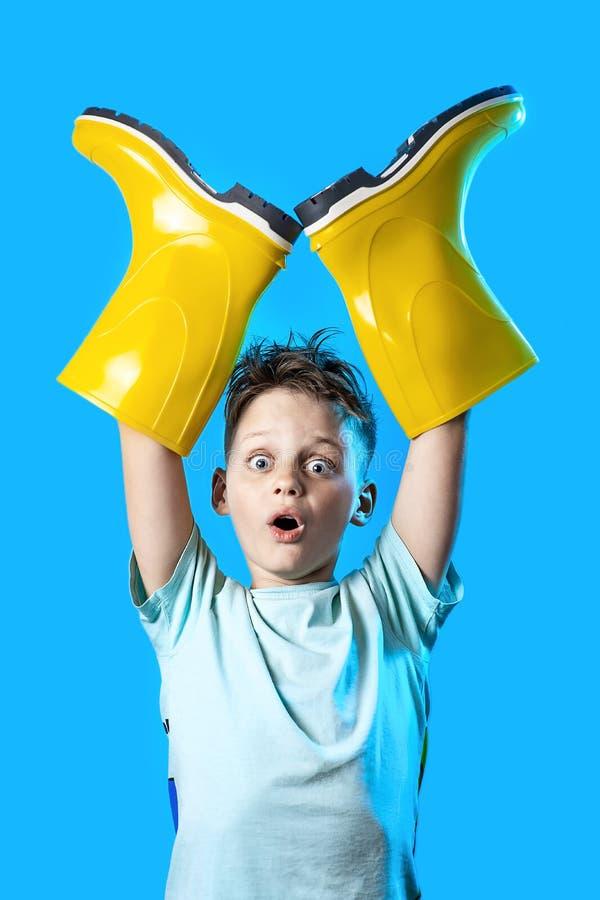 Überraschter Junge in einem hellen T-Shirt haftete seine Hände in den Gummistiefeln auf blauem Hintergrund stockbild
