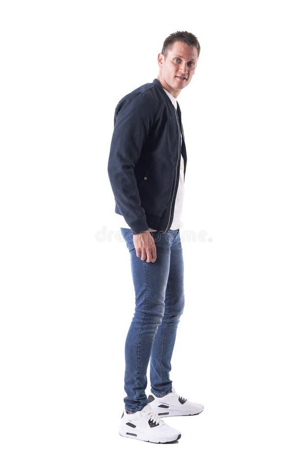 Überraschter junger erwachsener gutaussehender Mann in der Bomberjacke, die Kamera und Lächeln betrachtet Weicher Fokus stockbild