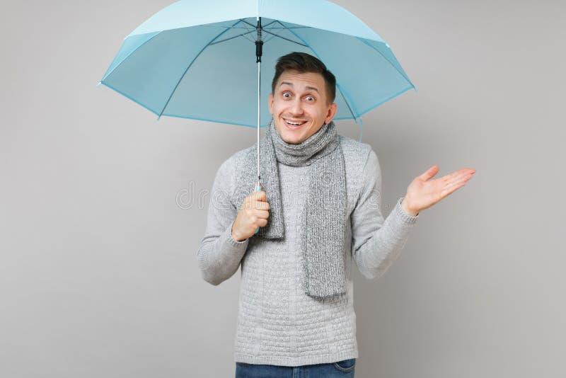 Überraschter junger Mann in der grauen Strickjacke, Schal zeigend, ausgebreiteter blauer Regenschirm der Handholding lokalisiert  lizenzfreies stockfoto