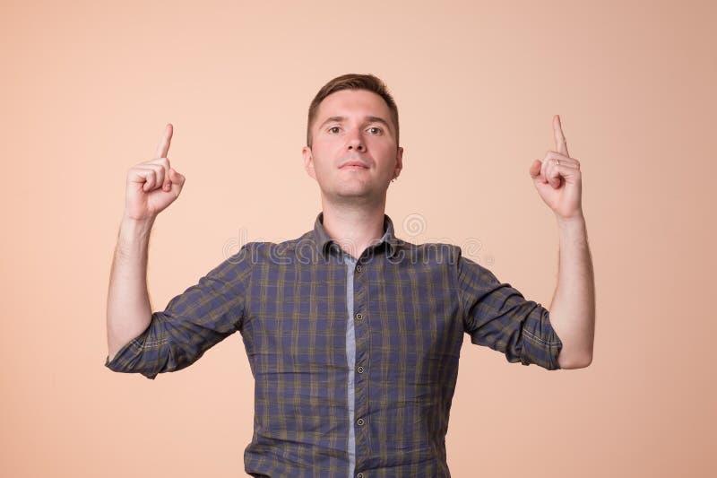 Überraschter junger Mann, der oben mit zwei Händen zeigt He schauen Sie oben Konzept stockfoto