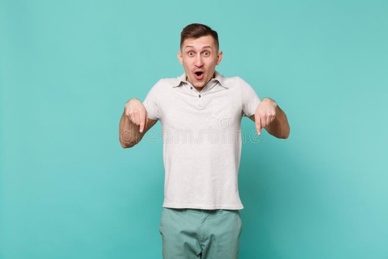 Überraschter junger Mann in der zufälligen Kleidung, die Mund offen, die Zeigefinger zeigend unten lokalisiert auf blauem Türkis  lizenzfreie stockbilder