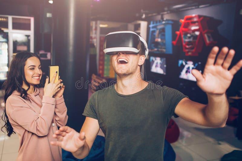 Überraschter junger Mann stehen und tragen VR-Gläser Er bewegt die emotionalen Hände wellenartig Junge Frau tiake Video auf Telef stockfotos