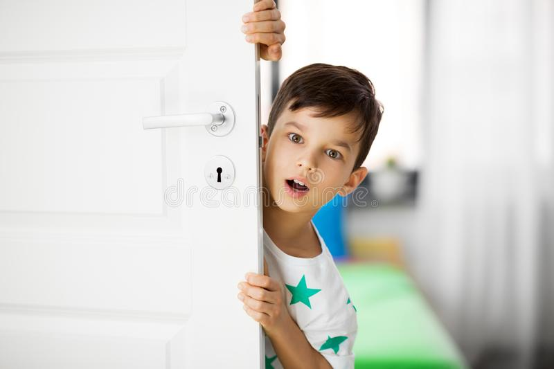 Überraschter kleiner Junge hinter Tür zu Hause lizenzfreie stockfotos