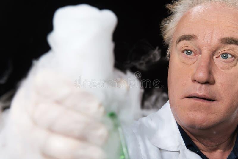 Überraschter Kliniker studiert im Labor und Haltenflasche lizenzfreie stockfotos
