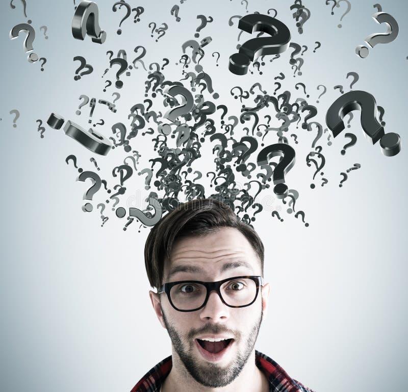 Überraschter Mann in den Gläsern Kopf und im Fragensturm stockbilder