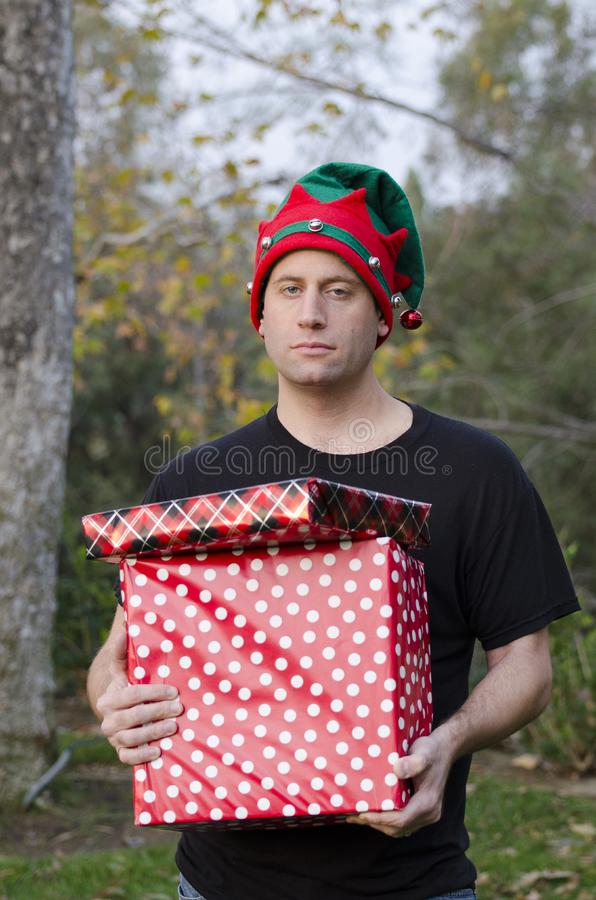 Überraschter Mann, der ein Weihnachtsgeschenk hält lizenzfreie stockfotografie