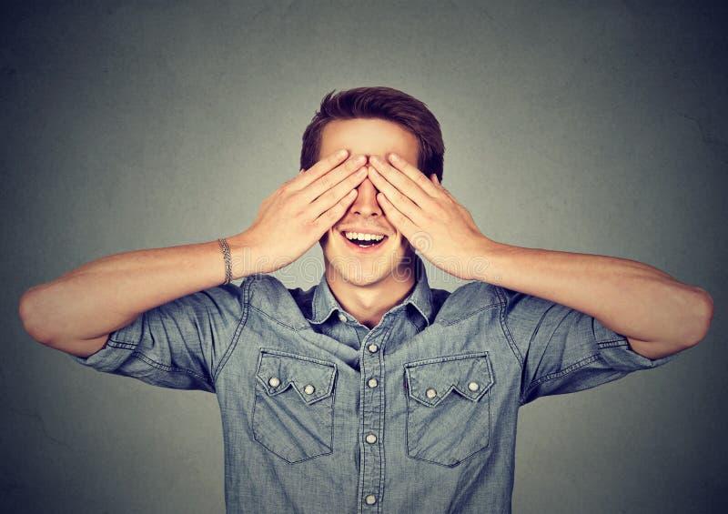 Überraschter Mann, der sein Augenlächeln umfasst stockfotografie