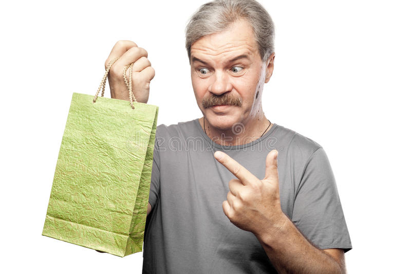 Überraschter reifer Mann, der Einkaufstasche lokalisiert auf Weiß hält lizenzfreie stockfotografie