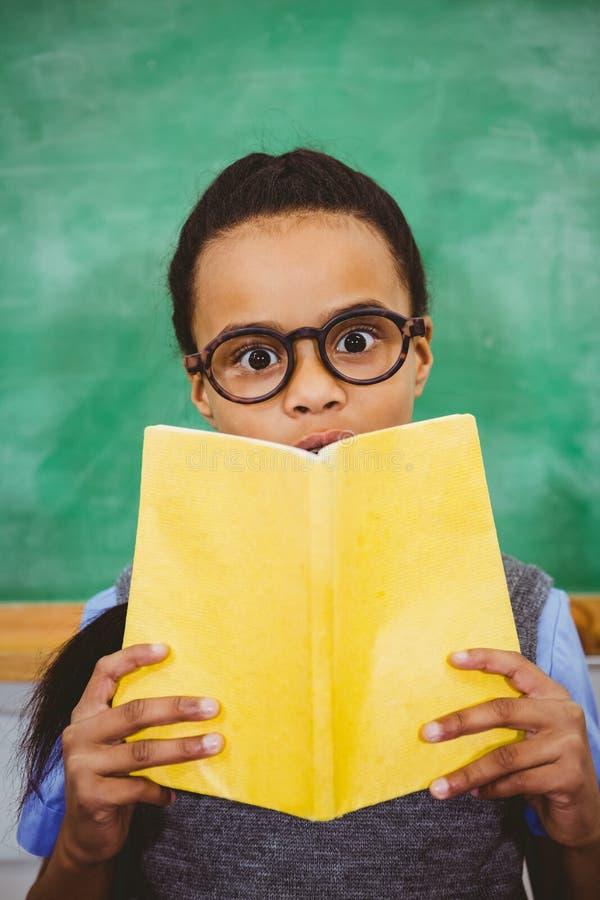 Überraschter Schüler, der Schulbuch hält lizenzfreie stockfotografie