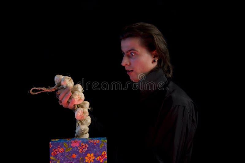 Überraschter Vampir mit dem Geschenkkasten, der Knoblauch herausnimmt stockfoto