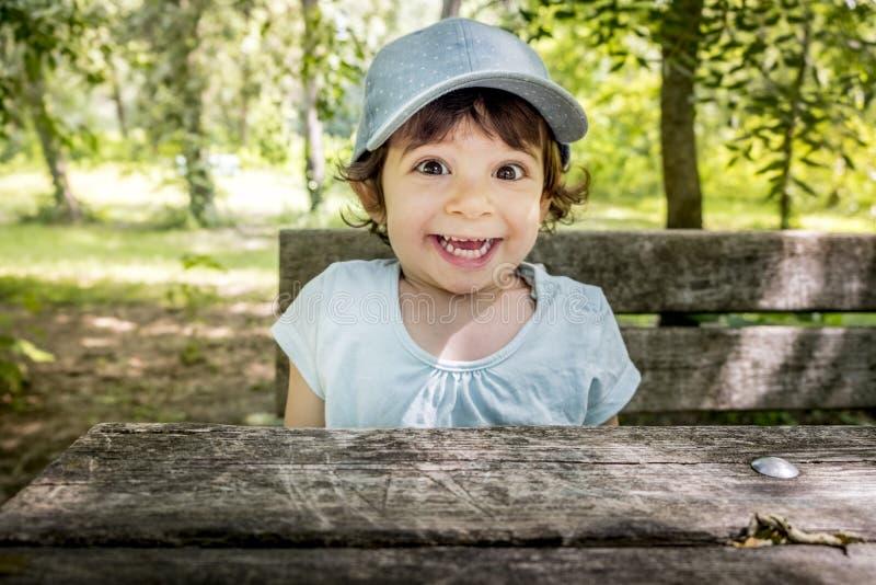 Überraschtes aktives freches glückliches Kind der Kinderlächelndes frohes Baby-Baseballmütze im Freien lizenzfreies stockfoto