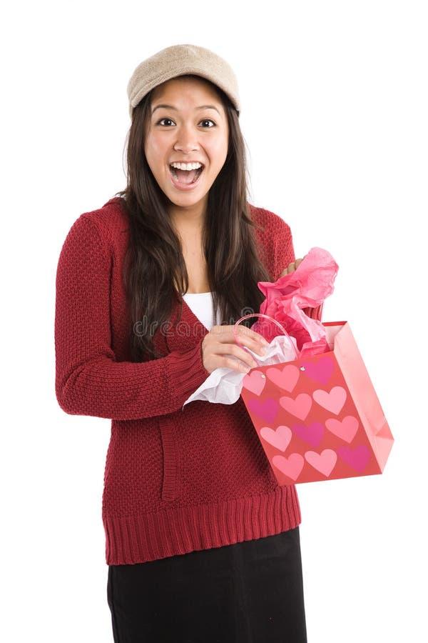 Überraschtes asiatisches Mädchen, das Valentinsgrußgeschenk empfängt lizenzfreies stockfoto