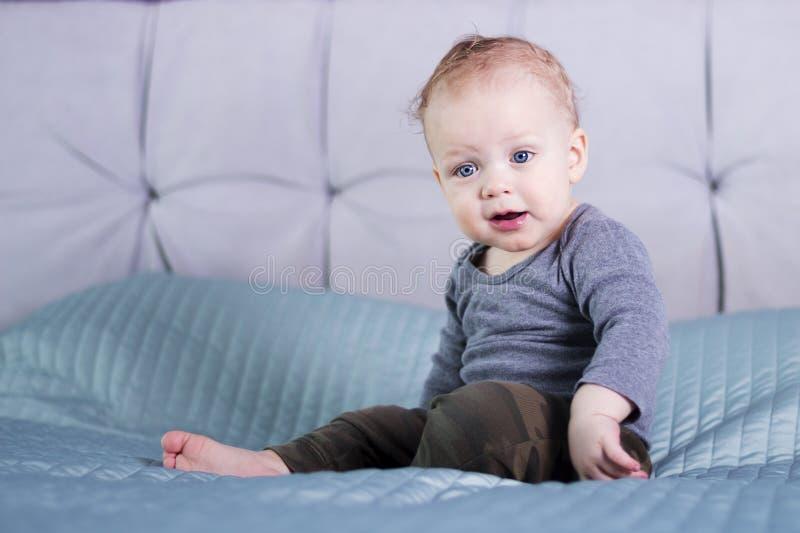 Überraschtes Baby, das auf dem Bett sitzt Säuglingskind mit dem Bitten um des Gesichtsausdrucks Kleinkindjungenbitten, was los is lizenzfreie stockbilder