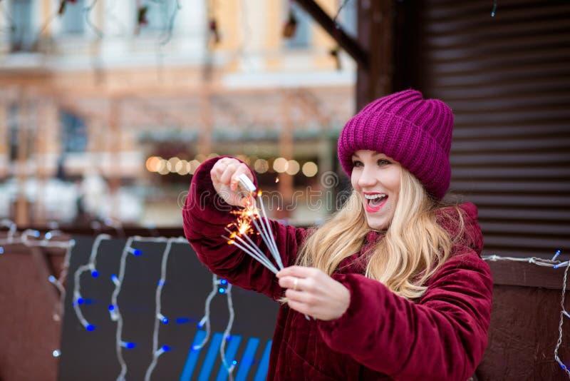 Überraschtes blondes Mädchen kleidete in der stilvollen Kleidung, legt Feuer auf gl an stockbilder