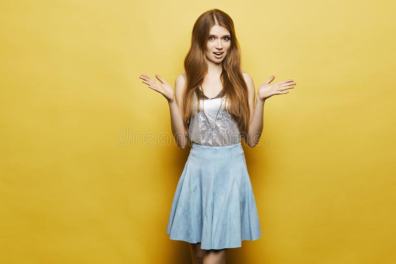 Überraschtes blondes vorbildliches Mädchen mit leichtem Make-up im stilvollen blauen Rock und in der modernen silbernen Bluse ste lizenzfreie stockbilder