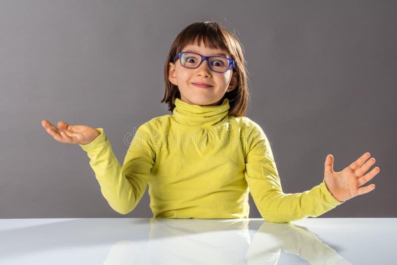 Überraschtes, fröhliches Kind mit Brillen, das eine aufregende Handgeste genießt stockfoto