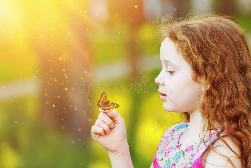 Überraschtes gelocktes Mädchen mit einem Schmetterling auf seinem Finger lizenzfreie stockbilder