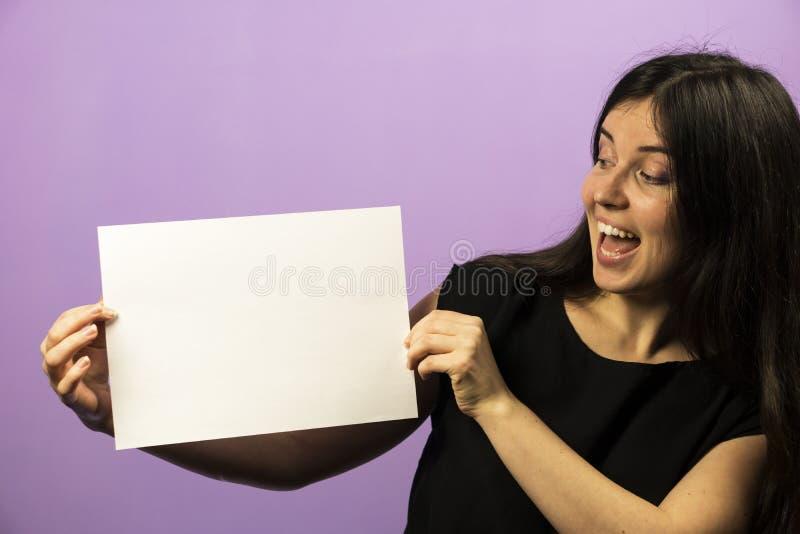 Überraschtes junges Brunette-Mädchen, das leeres leeres weißes Brett hält Broschürendarstellung Flugschriftgriffhände Mädchenshow stockbilder