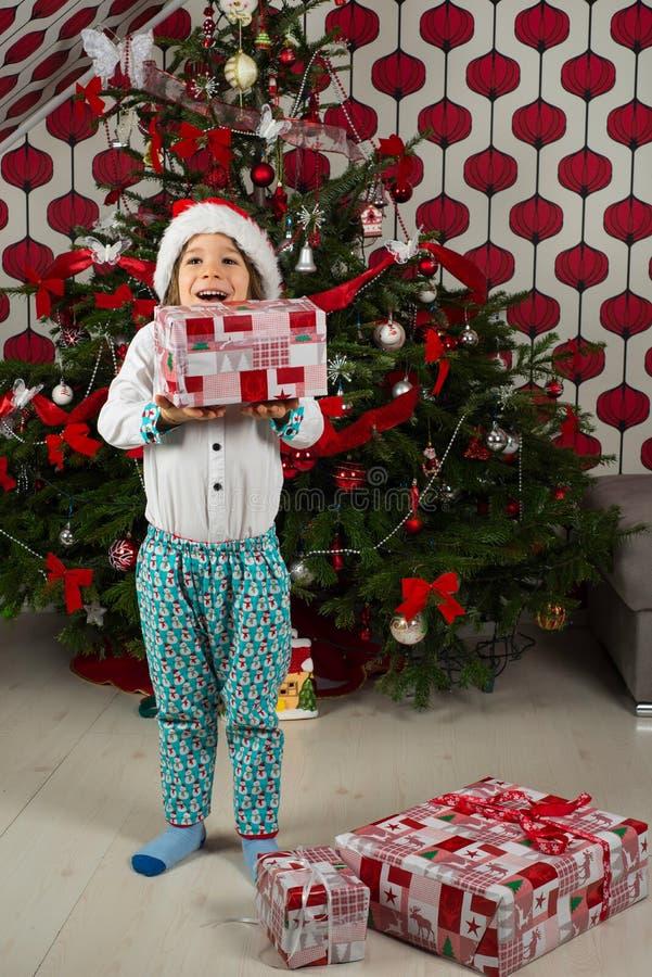 Überraschtes Kind, das Weihnachtsgeschenke hält stockbilder