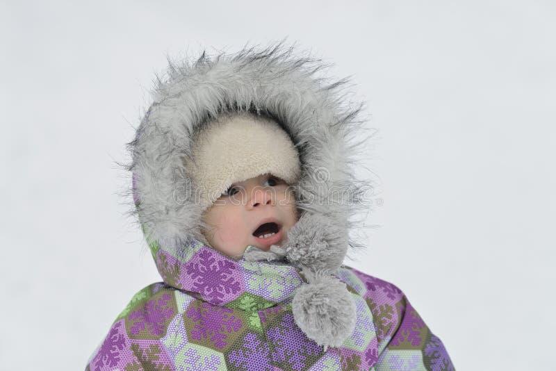 Überraschtes Kind in der warmen Kleidung am schneebedeckten Hintergrund des Winters stockfoto