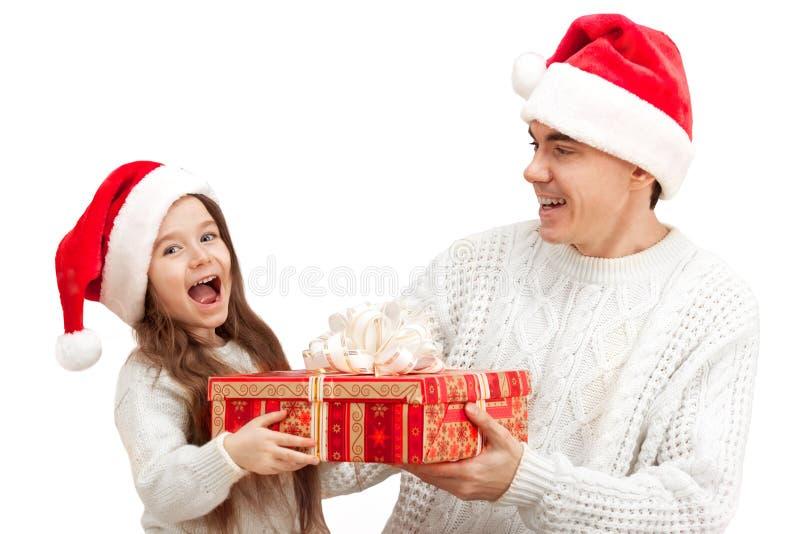Überraschtes Kind mit ihrem Vater, der ein Geschenk hält stockfotos