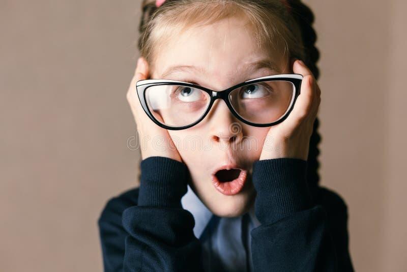 Überraschtes kleines Mädchen mit Gläsern stockfotos