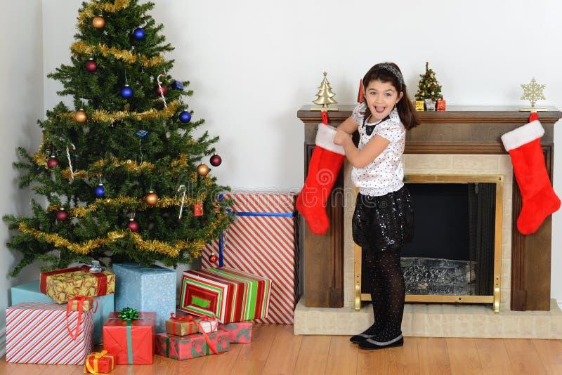 Überraschtes kleines Mädchen mit Weihnachtsstrumpf stockfotos