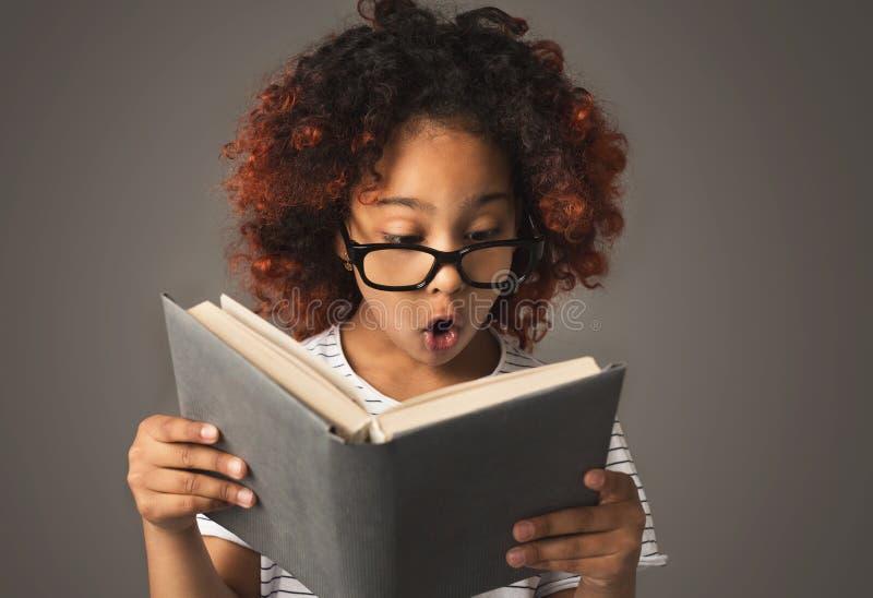Überraschtes kleines schwarzes Mädchen mit Buch am grauen Hintergrund lizenzfreie stockfotografie