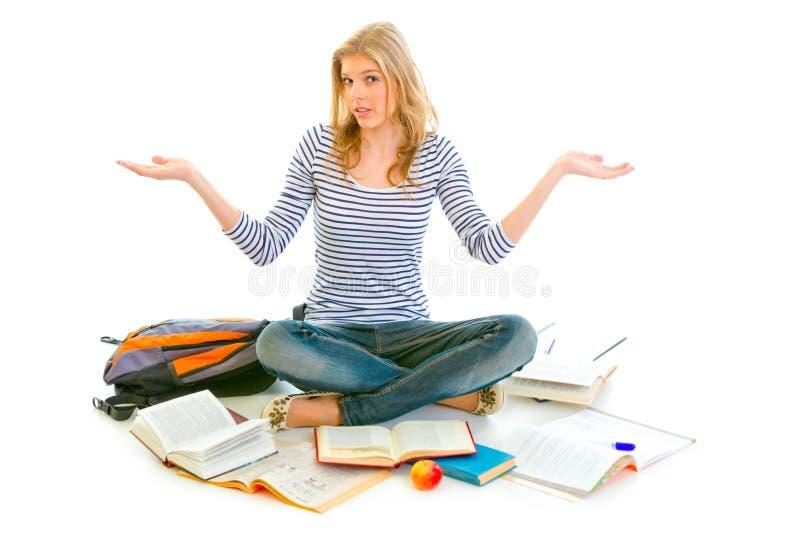 Überraschtes Mädchen auf dem Fußboden umgeben durch Bücher lizenzfreie stockfotografie