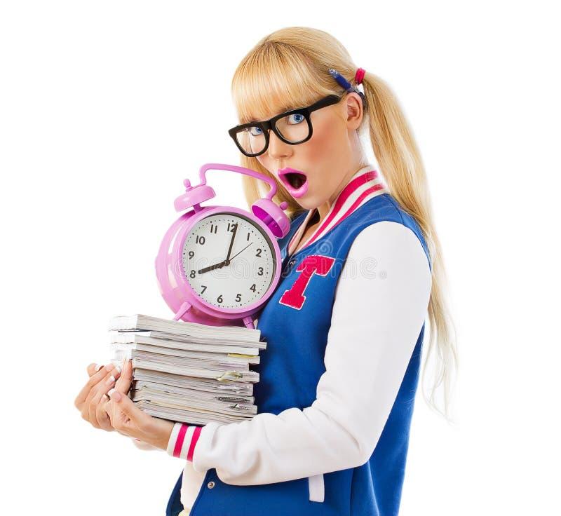Überraschtes Mädchen, das Bücher und Uhr hält stockbilder