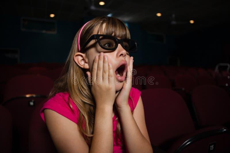 Überraschtes Mädchen, das Gläser 3D beim Aufpassen des Films trägt stockbild