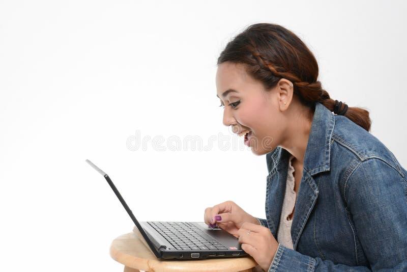 Überraschtes Mädchen, das im Laptop schaut lizenzfreie stockfotos