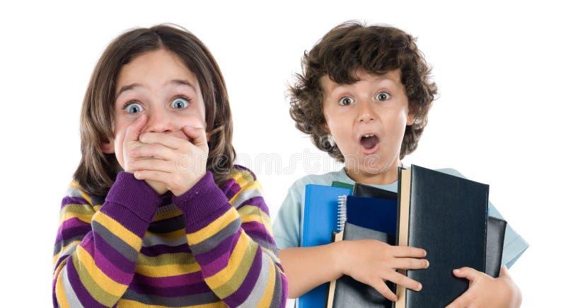 Überraschtes Mädchen und ein Junge mit dem Fallen vieler Bücher lizenzfreie stockfotografie
