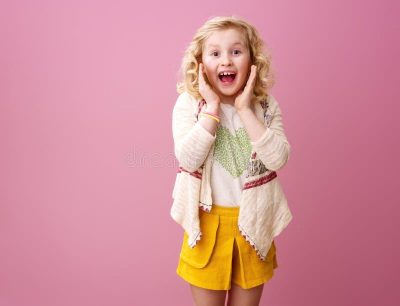 Überraschtes modernes Mädchen mit dem gewellten blonden Haar lokalisiert auf Rosa stockfotografie