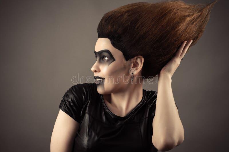 Überraschtes rührendes üppiges Haar der Brunettefrau auf Kopf stockbild