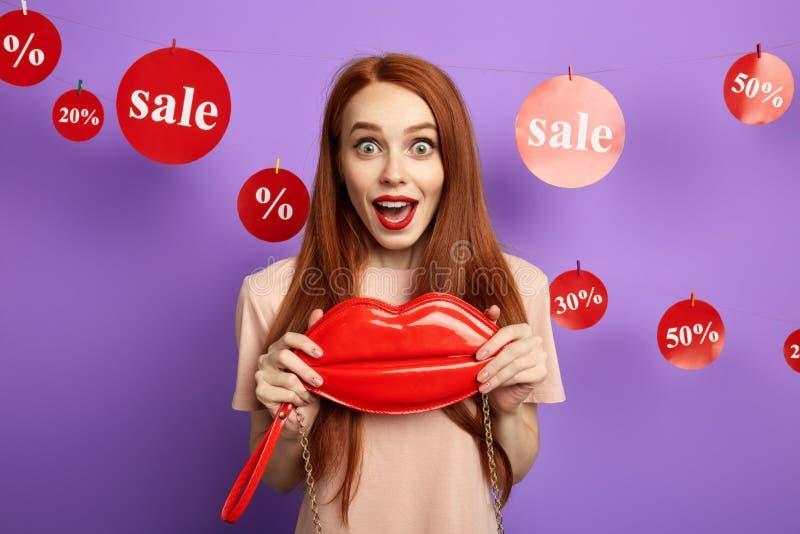 Überraschtes rotes Haarmädchen, das positiven Ausdruck zeigt stockfoto