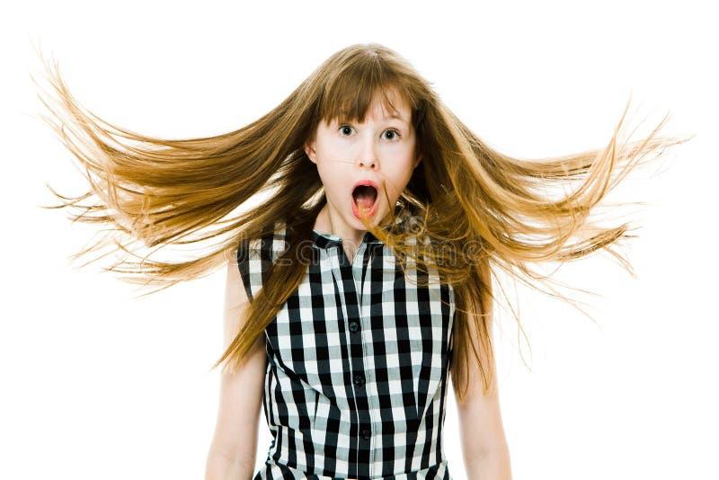 Überraschtes teenaged Mädchen mit den langen geraden fliegenden Haaren tragen schwarzes kariertes Kleid stockfotografie