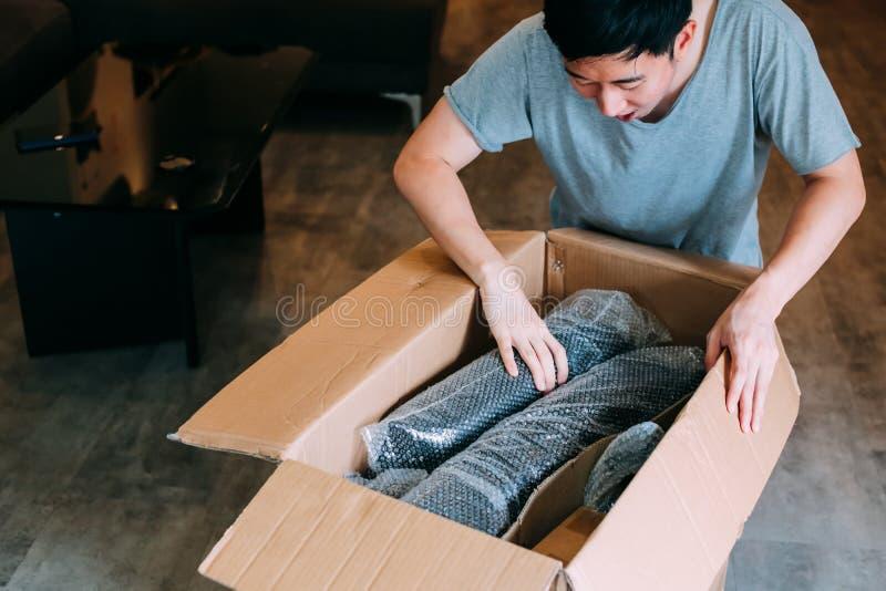 Überraschtes unboxing Paket des asiatischen Mannes zu Hause lizenzfreies stockfoto