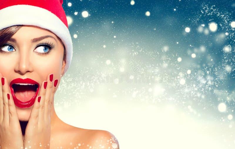 Überraschtes Weihnachtsmädchen Schönheitsfrau in Sankt-` s Hut stockfotografie