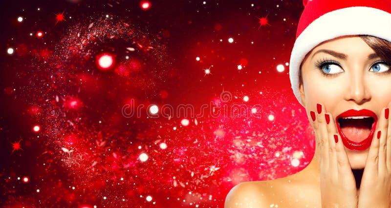 Überraschtes Weihnachtsmädchen Schönheitsfrau in Sankt-` s Hut stockbild