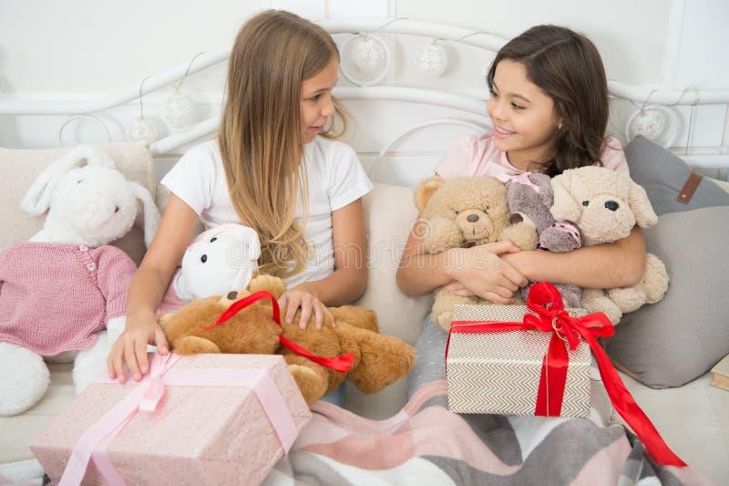 Überraschung des neuen Jahres Glückliche kleine Kinder halten Geschenkboxen Nette kleine Mädchen mit Geschenken im Bett Öffnung s lizenzfreie stockfotografie