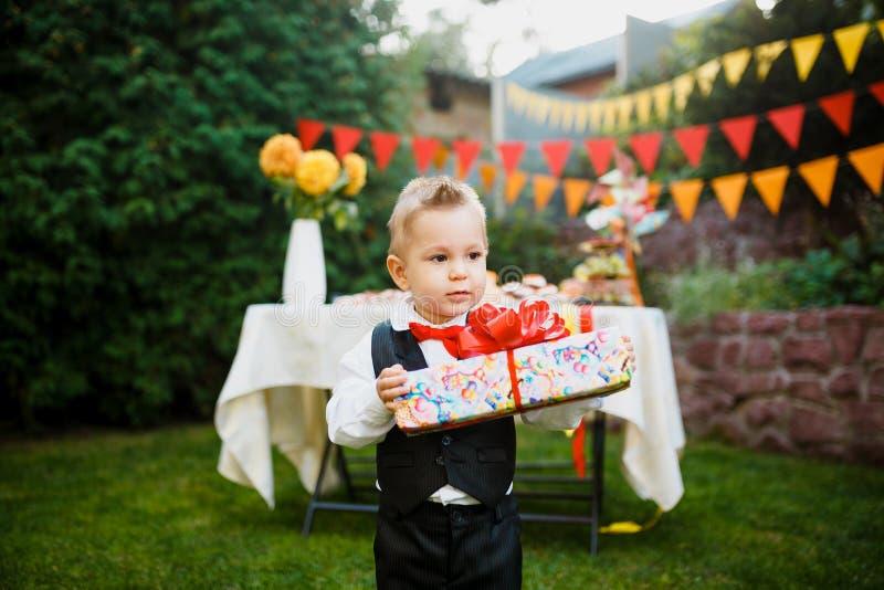 Überraschung für den Geburtstag der Junge hält einen Kasten mit einem Geschenk im Yard auf dem Hintergrund einer festlichen Tabel stockfoto