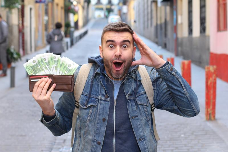 Überraschungsmann mit voller Geldbörse stockbilder