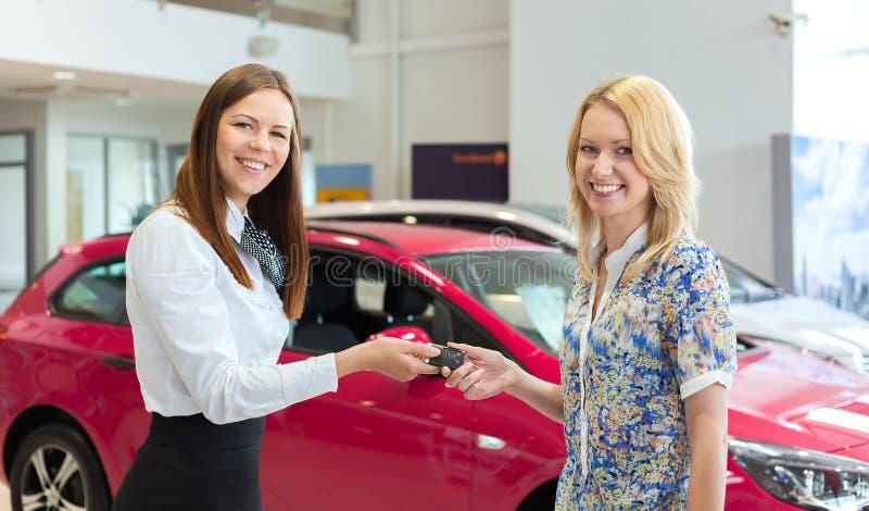 Überreichende Autoschlüssel der glücklichen Verkäuferin zum attraktiven jungen weiblichen Inhaber des Neuwagens lizenzfreies stockbild