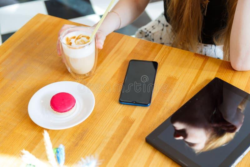 Überreicht Laptopsmarttelefon und -tablette mit Kaffee auf dem Tisch im modischen Café stockfoto