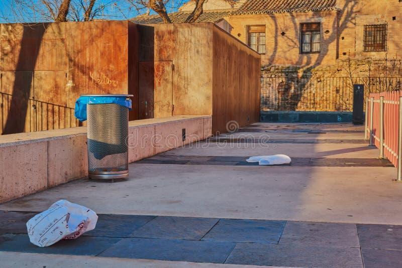 Überreste des Abfalls und des Abfalls der Plastiktaschen und Abfalleimer bei Sonnenaufgang in einem Park in Toledo, Kastilien La  lizenzfreie stockfotos