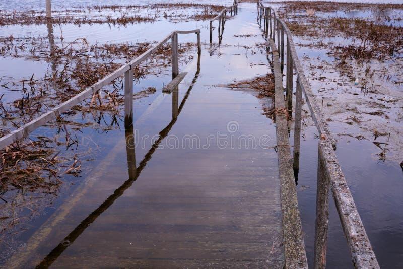 Überschwemmte Holzbrückeplanken, als Symbol und Konzept der Verwüstung der verlorenen Hoffnungen und des hohen Alters Ruhiger Flu stockfotos